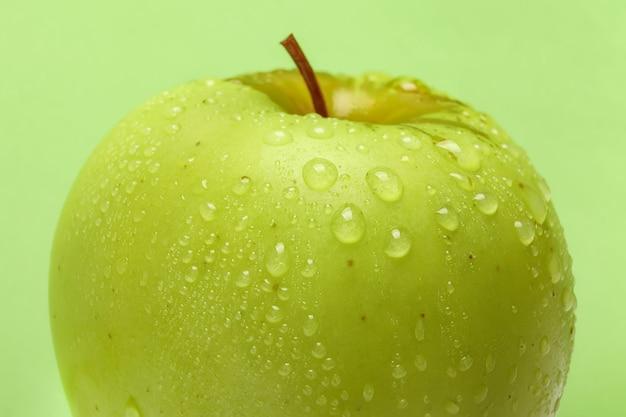 緑の背景に新鮮な青リンゴの水滴のクローズアップ