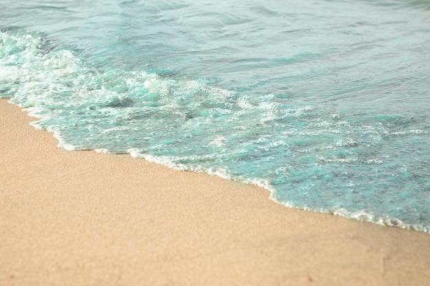 熱帯の砂浜のビーチで水のクローズアップ