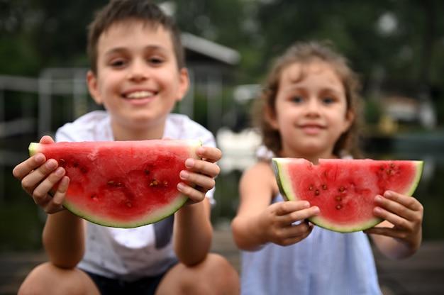 川の背景の桟橋で休んで、美しい子供たちの広げられた手でスイカのスライスのクローズアップ。田舎の夏休みのコンセプト
