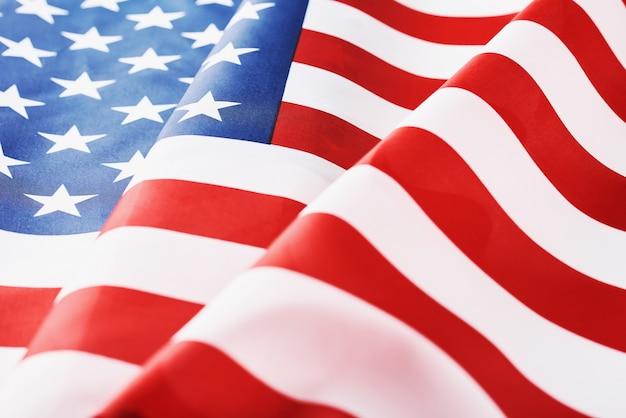 背景としてアメリカ国旗を振ってのクローズアップ。記念または独立記念日または7月4日の概念