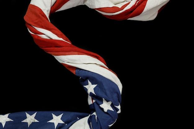 黒の背景にアメリカのアメリカの国旗を振ってのクローズアップ。