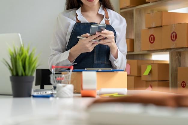 自宅でオンラインのテーブル販売コンセプトで小包ボックス付きスマートフォンを保持しているエプロン実業家を身に着けているのクローズアップ。