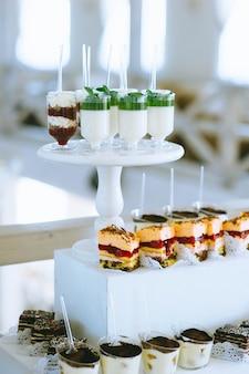さまざまな色の明るいカップケーキ、マカロン、ケーキ、ゼリー、フルーツの結婚式のキャンディーバーのクローズアップ。お菓子やその他のデザートを使った甘いホリデービュッフェ。
