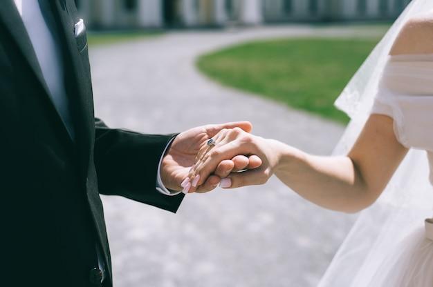屋外で手をつないでいる結婚式のカップルのクローズアップ。背景がぼやけている。