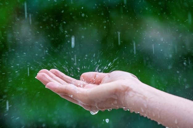 雨の中で濡れた女性の手のクローズアップ