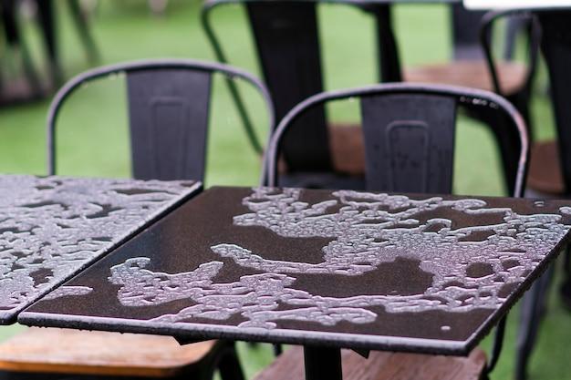 정원 잔디에 자리 잡은 젖은 철제 테이블과 의자를 닫습니다.