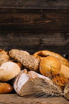 나무 테이블에 구운 빵 앞에서 밀 작물의 클로즈업