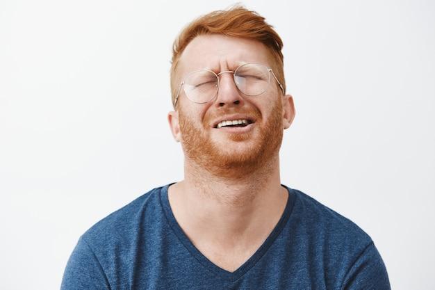 Крупный план скулящего упрямого рыжего бородатого мужчины, который выглядит несчастным, жалуется и плачет