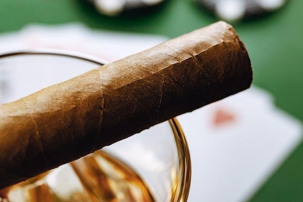 Крупным планом бокал виски и сигары на зеленой поверхности