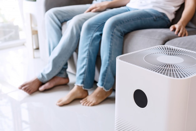 Крупным планом белый очиститель воздуха на полу в гостиной на фоне молодой азиатской пары расслабляется на диване