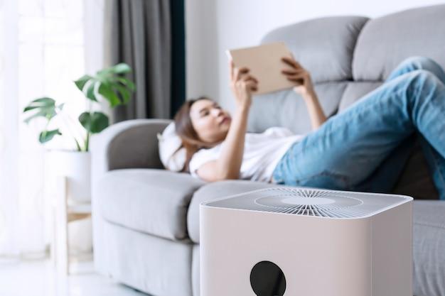Крупным планом белого очистителя воздуха на полу в гостиной на фоне молодой азиатской женщины расслабляется
