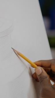花瓶の描画と黒い手で白い帆布のクローズアップ