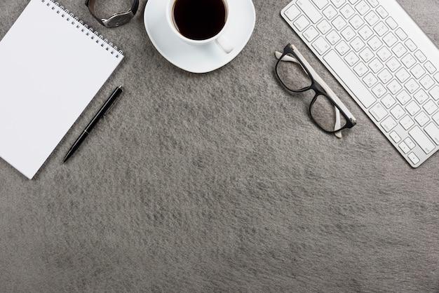 Крупный белый кофейная чашка; клавиатура; наручные часы; ручка; спиральный блокнот; очки и клавиатура на столе