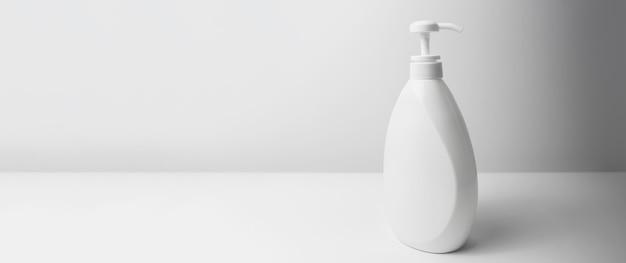 白いスタジオの背景に白いディスペンサーボトルのクローズアップ。