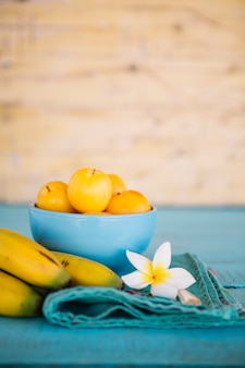 Close-up of white flower; banana and plums on blue wooden table top