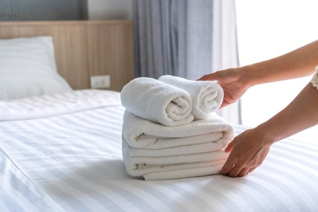 Закройте белые постельное белье отеля и набор полотенец. обслуживание номеров. гостиничный бизнес-концепция.