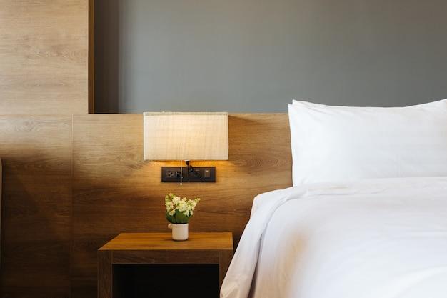 Конец-вверх белой подушки на украшении кровати с светлой лампой в интерьере спальни гостиницы.