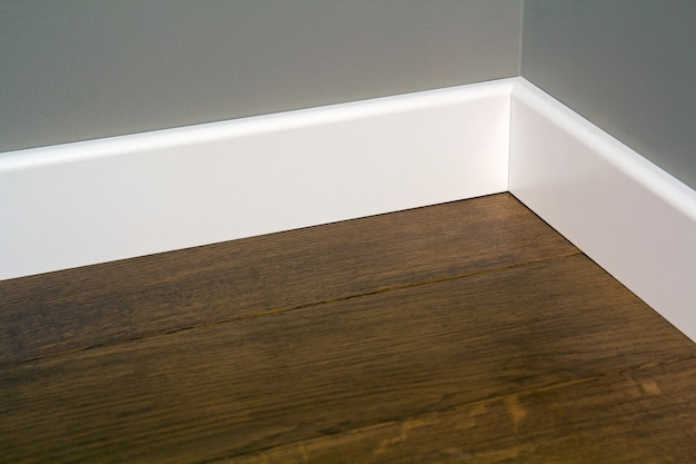 어두운 나무 오크 바닥 마루에 흰색 플라스틱 plinths의 닫습니다.