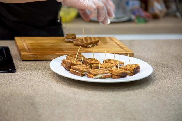 Закройте белые тарелки закусок на гриле бутерброды. фон - кухня и руки повара в резиновых перчатках, мягкий фокус, размытие