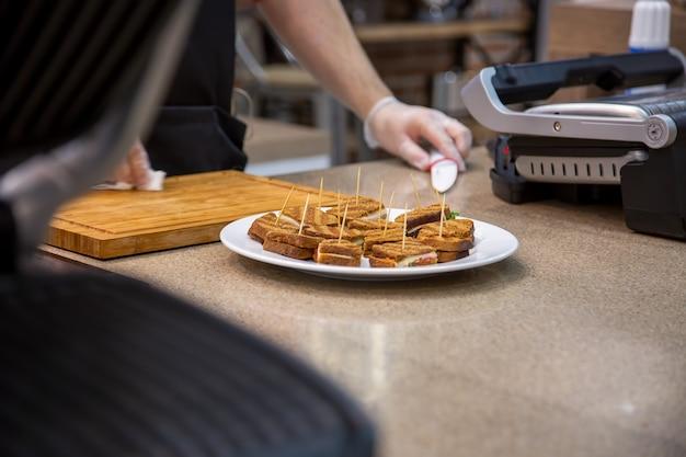 Закройте белые тарелки закусок на гриле бутерброды. фон - кухня и руки повара в резиновых перчатках с ножом, мягкий фокус, размытие