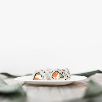 Close-up of white plate with sushi on wooden table against white backdrop