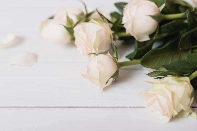 木製のテーブルに白いバラのクローズアップ