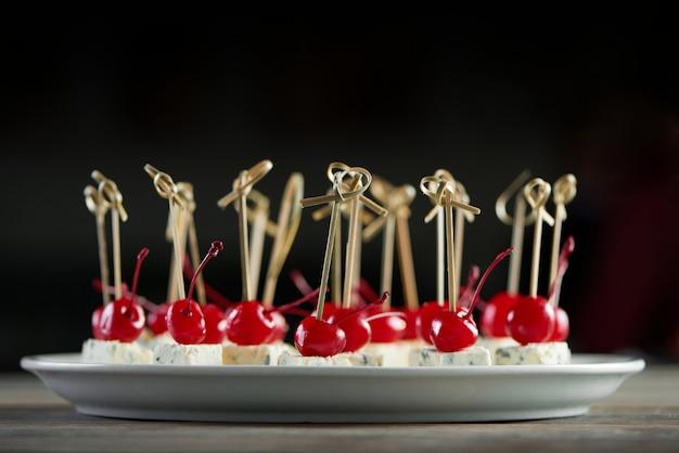 Крупный план белой круглой тарелки, полной восхитительных закусок с красной коктейльной вишней и кусочками голубого сыра. хорошая закуска для кейтеринга с легким алкоголем или ресторанного шведского стола.