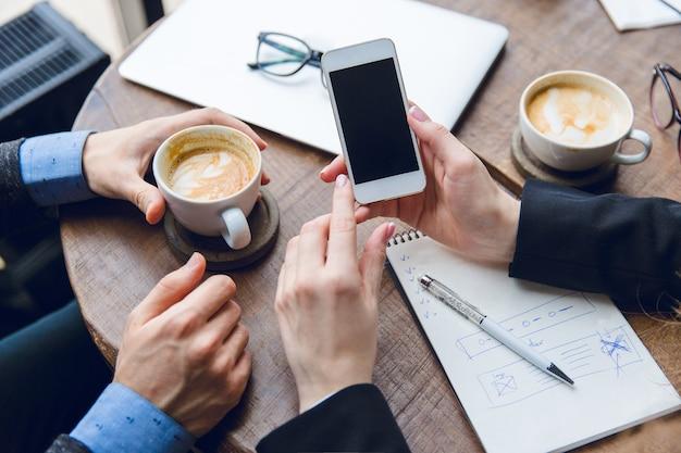 Крупный план белого смартфона в руках женщины. двое коллег сидят за журнальным столиком и пьют кофе