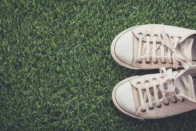緑色の草の上に白いスニーカーのビンテージフィルターとの背景