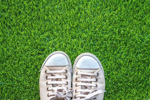 緑色の草の背景に白いスニーカーのクローズアップ