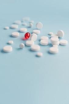 Закройте белые таблетки с красным капсулы лекарства
