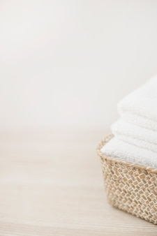 Close-up of white towels in basket on wooden tabletop