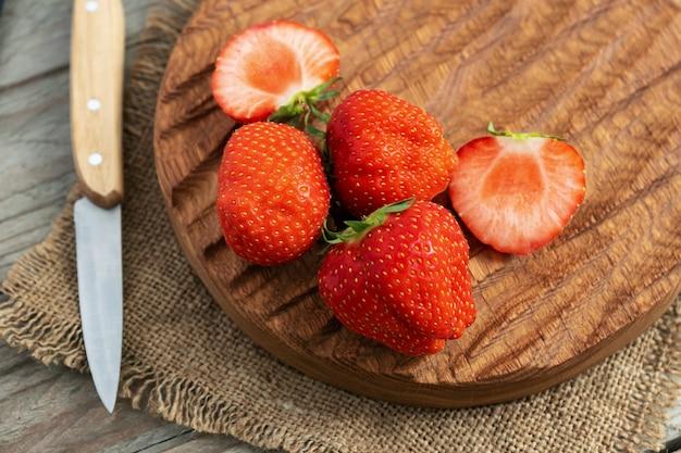 Закройте целую и нарежьте свежую красную клубнику на дубовой разделочной доске с ножом
