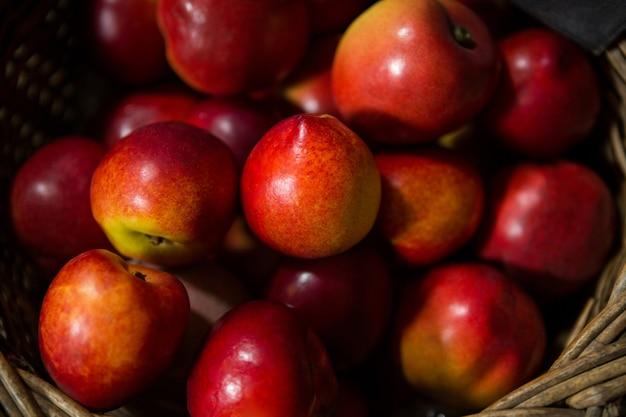 Крупный план плетеной корзины, полной яблок