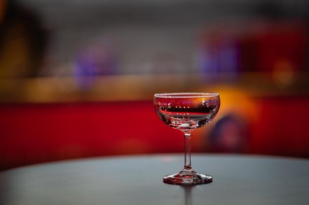 パブの常夜灯の赤い背景の上のワイングラスのクローズアップ
