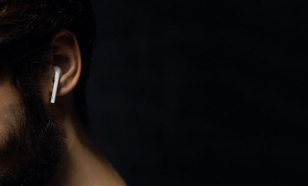 コピースペースのある黒い色の壁に男性の耳のワイヤレスイヤホンのクローズアップ。