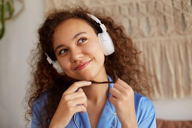 Закройте желаемое кудрявый мулат молодой женщины, слушающей любимую романтическую музыку в наушниках, наслаждаясь воскресным утром, мечтательно смотрит в сторону.