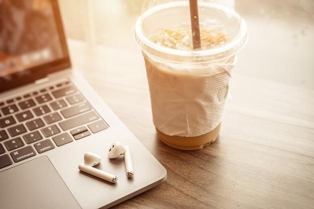 Крупный план с чашкой кофе, работающей с портативным компьютером и наушником с изолированным на деревянном фоне, офисном столе в кафе, как фон