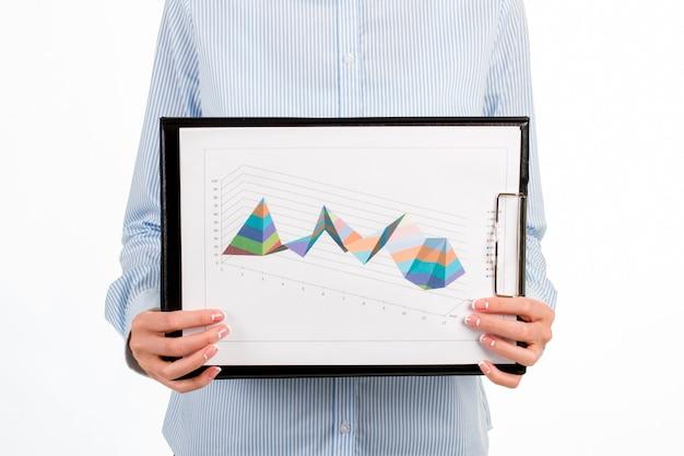 여성의 그래픽 차트의 클로즈업입니다. 다이어그램으로 클립보드를 보여주는 사업가. 우리가 얼마나 멀리 왔는지. 확실히 작년보다 나아졌습니다.
