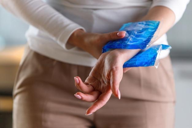 コンピューター、ラップトップでの長時間の仕事によって引き起こされる痛みを伴う手首に冷湿布を適用する女性のクローズアップ