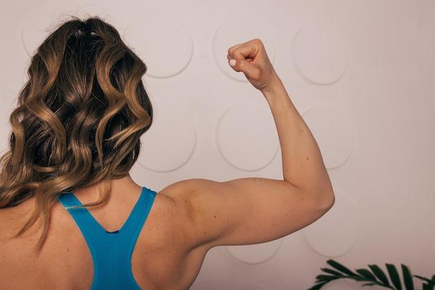 Закройте женщину обратно с сгибанием мышц. культуристка с идеальным бицепсом.
