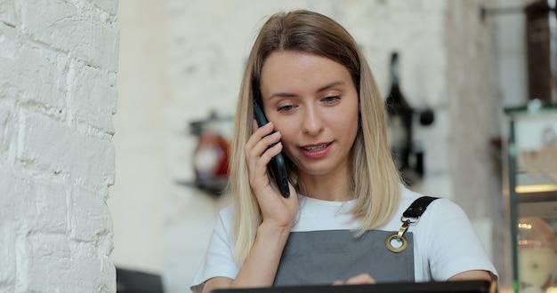 コーヒーショップの女性バリスタのクローズアップは、携帯電話での予約注文を受け付け、カフェのラップトップコンピューターに書き留めます。配達食品ホームオンライン注文の概念。