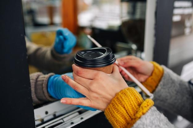 コーヒーを購入し、バリスタの売り手の手から紙コップを取る女性のクローズアップ。