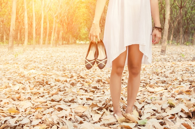 Крупным планом женщина несла свои туфли в руке
