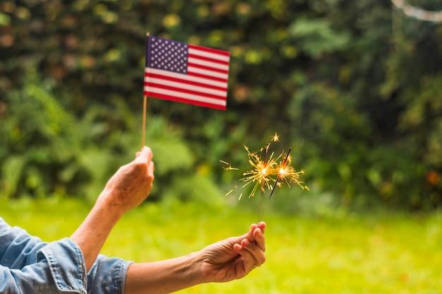 Конец-вверх женщины празднуя день независимости держа флаг сша и искры огня