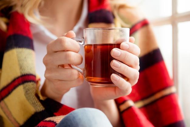 Заделывают женщины, покрывающей плед и держащей чашку чая