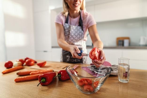 健康的な昼食のために有機トマトを切る女性のクローズアップ。