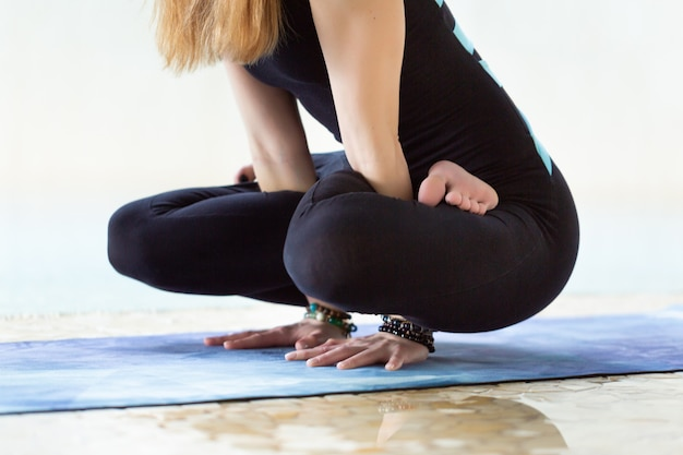 Крупным планом женщины делают позы йоги, руки жест возле бассейна