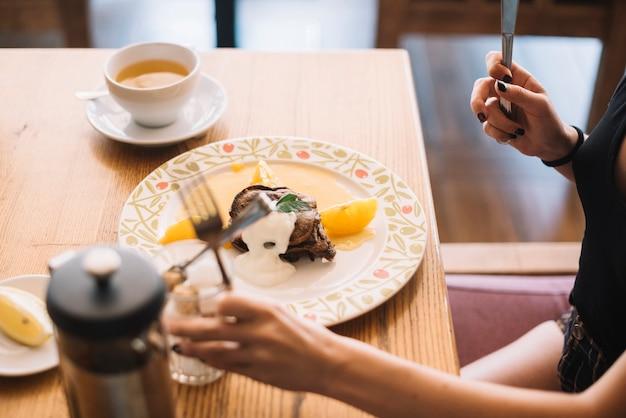 Крупным планом женщина завтракает в ресторане