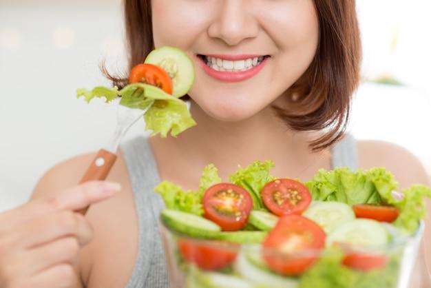 新鮮なサラダを食べる女性のクローズアップ